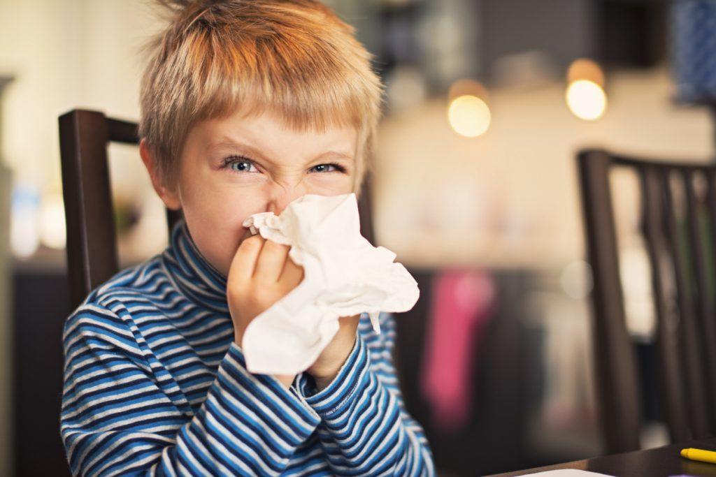 boy cleaning nose with tissue
