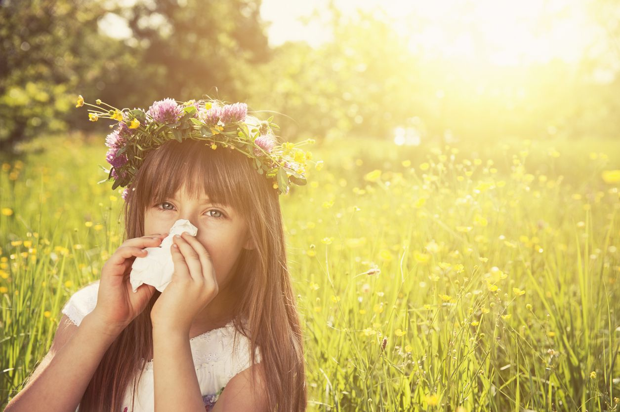 girl cleaning nose with a tissue in grass