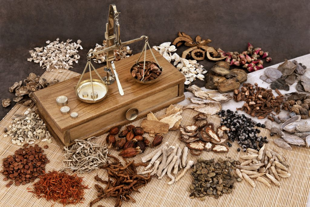 Traditional chinese herbal medicine selection with herb ingredients and old scales.